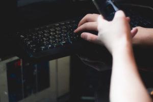 パソコンで作業中の男性の手クローズアップ。